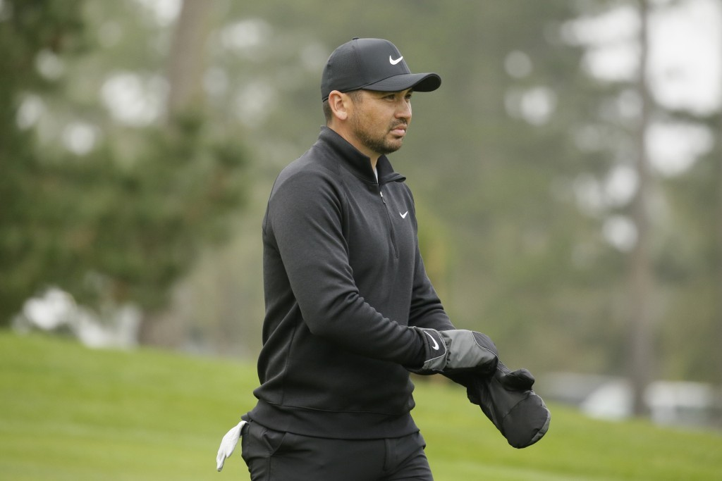 Jason Day, of Australia, puts on mittens while walking down the 10th fairway of the Spyglass Hill Golf Course during the third round of the AT&T Pebbl...