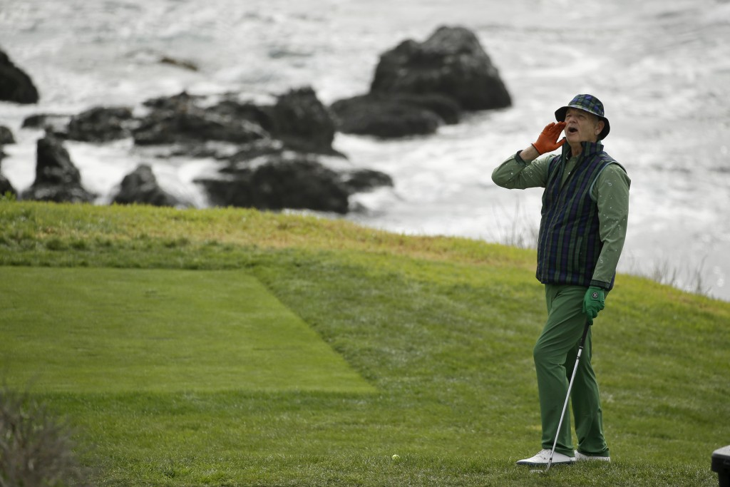 """Bill Murray yells """"Fore!"""" to spectators before hitting from the eighth tee back to the sixth green of the Pebble Beach Golf Links during the third rou..."""