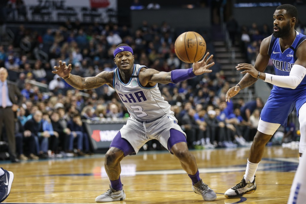 Charlotte Hornets guard Terry Rozier, left, beats Dallas Mavericks guard Tim Hardaway Jr. to a loose ball during the first half of an NBA basketball g...