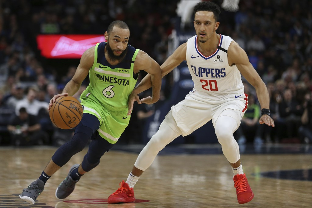 Minnesota Timberwolves' Jordan McLaughlin (6) drives the ball around Los Angeles Clippers' Landry Shamet in the first half of an NBA basketball game S...
