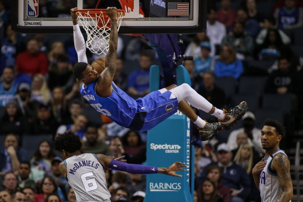 Dallas Mavericks guard Delon Wright dunks above Charlotte Hornets forward Jalen McDaniels (6) during the first half of an NBA basketball game in Charl...