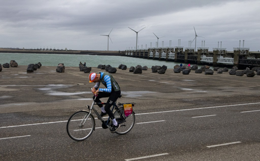 A competitor battles gale force winds during the Dutch Headwind Cycling Championships on the storm barrier Oosterscheldekering, rear, near Neeltje Jan...