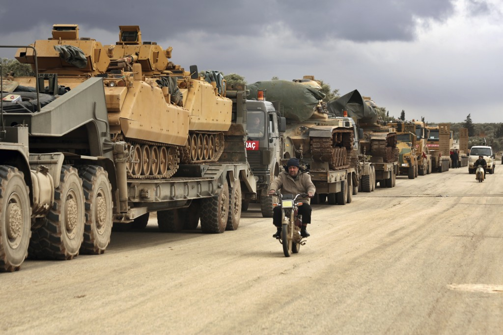 Turkish military convoy drives through the village of Binnish, in Idlib province, Syria, Saturday, Feb. 8, 2020. Several Turkish armored vehicles and ...