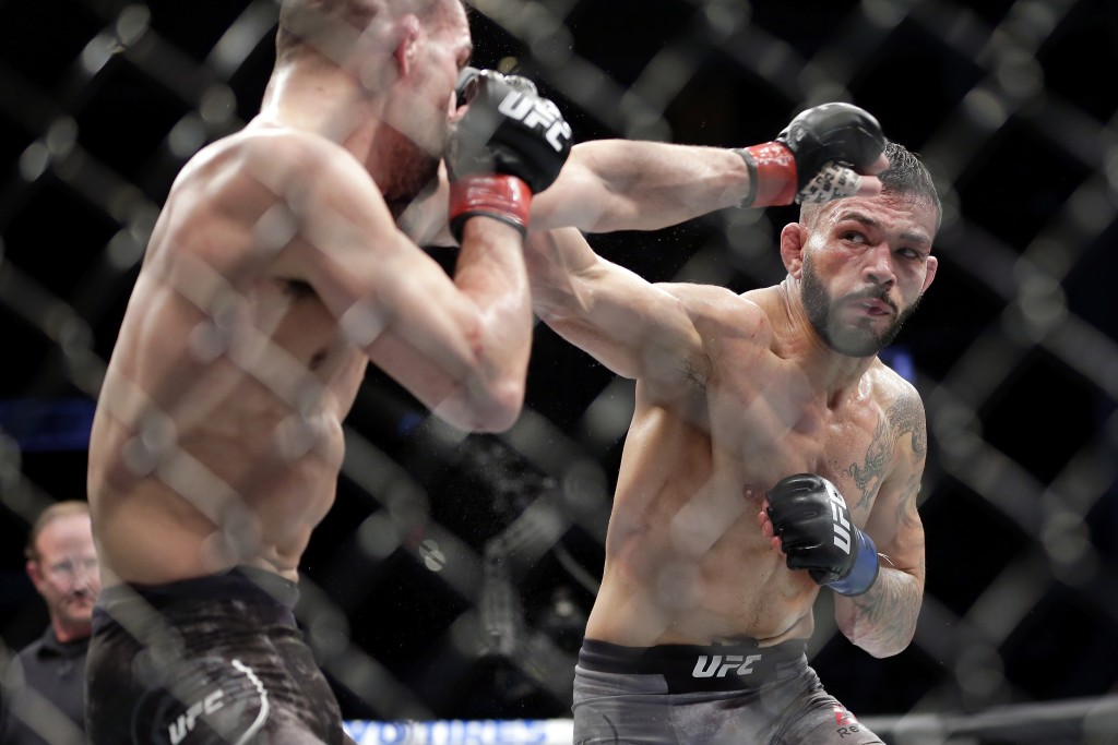 Mirsad Bektic, left, defends the punch by Dan Ige during the third round of a featherweight mixed martial arts bout at UFC 247 on Saturday, Feb. 8, 20...