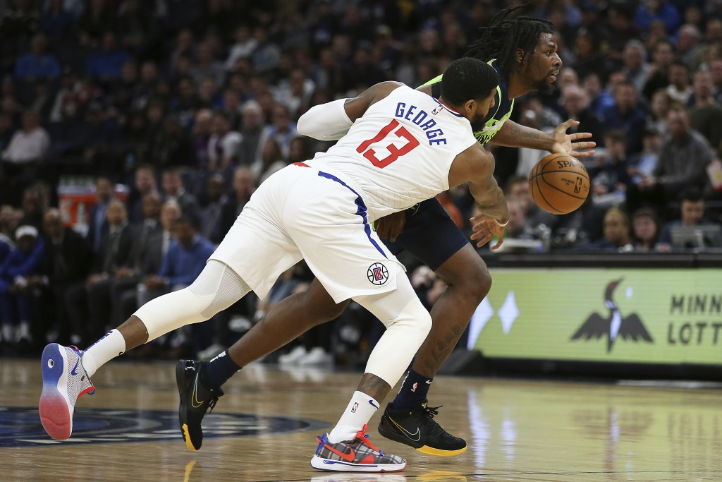 Los Angeles Clippers' Paul George (13) knocks the ball out of the hands of Minnesota Timberwolves' Naz Reid in the first half of an NBA basketball gam...