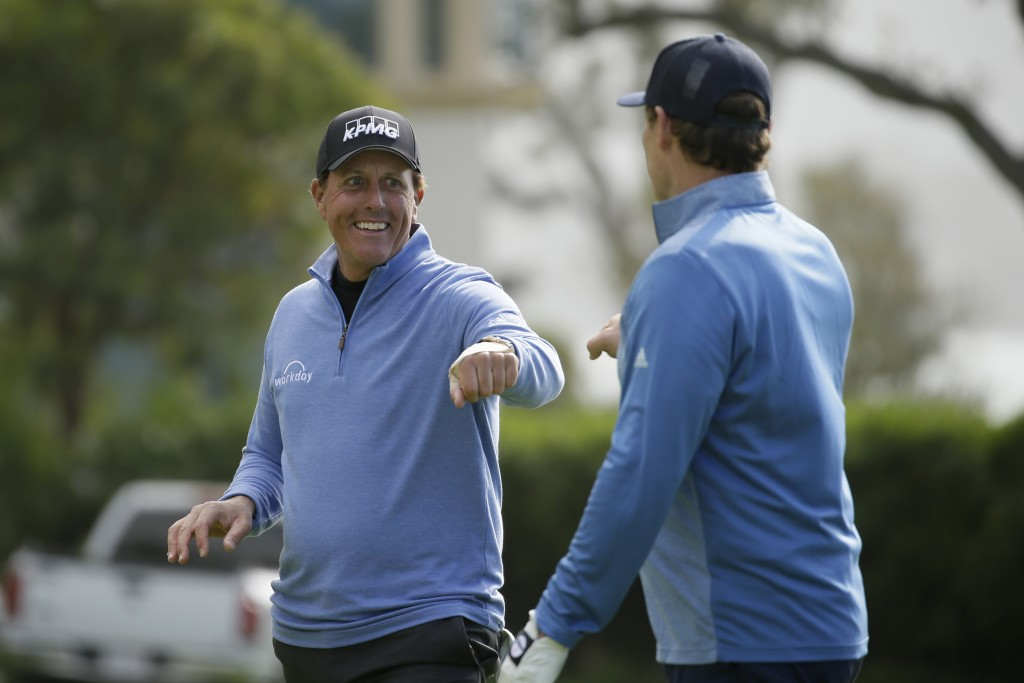 Phil Mickelson is greeted by Steve Young after chipping the ball into the 14th hole of the Pebble Beach Golf Links for a birdie during the third round...