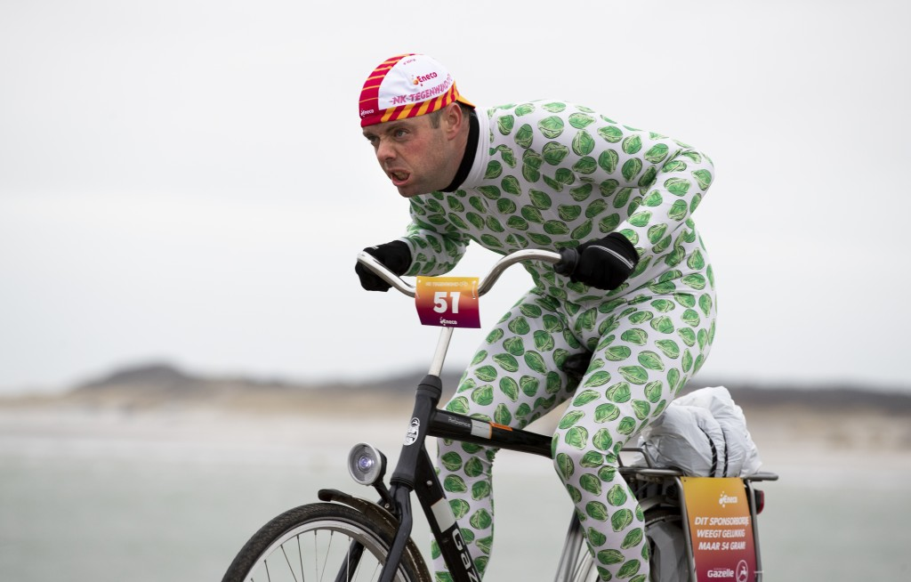 A competitor wearing a onesie with Brussels sprouts battles gale force winds during the Dutch Headwind Cycling Championships on the storm barrier Oost...