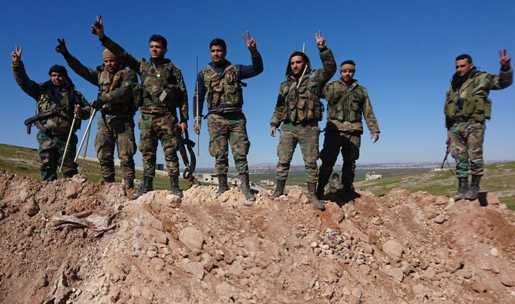 In this photo released by the Syrian official news agency SANA, Syrian army soldiers flash the victory sign in the village of al-Eis, in Aleppo provin...