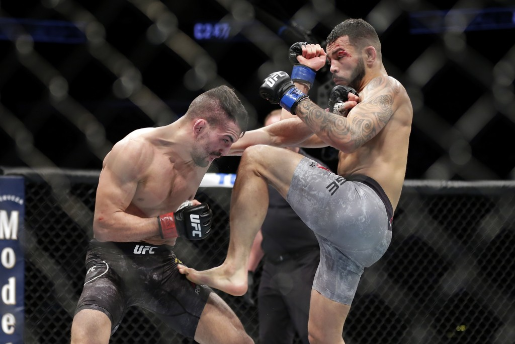 Mirsad Bektic, left, punches as Dan Ige, right, throws a knee during a featherweight mixed martial arts bout at UFC 247 on Saturday, Feb. 8, 2020, in ...
