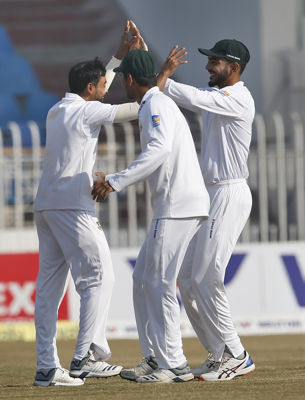 Bangladesh pacer Abu Jayed, left, celebrates with teammates after taking the wicket of Pakistan batsman Babar Azam during the third day of their 1st t...
