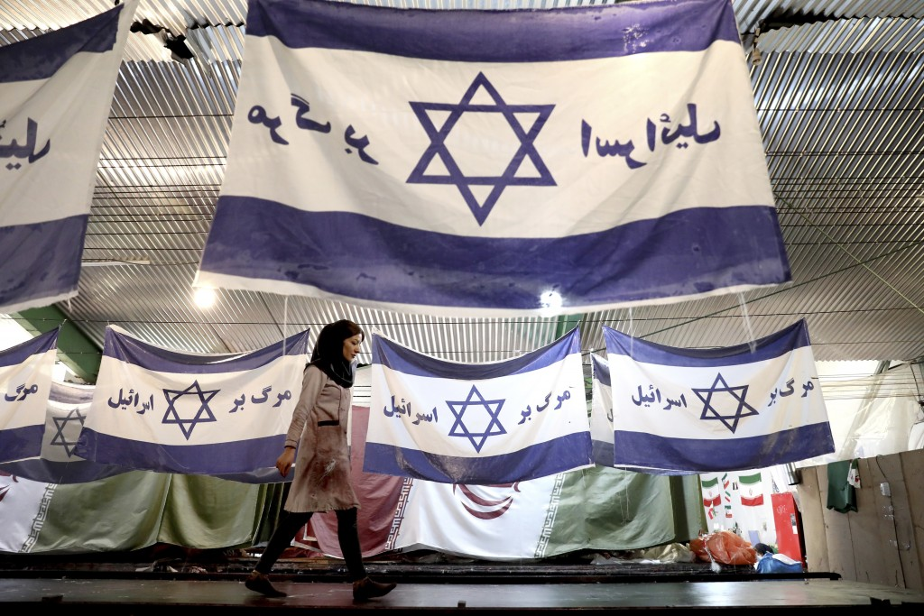 """In this Saturday, Feb. 8, 2020 photo, a worker walks past Israeli flags with a slogan in Persian which reads, """"Death to Israel,"""" at the Diba Parcham K..."""