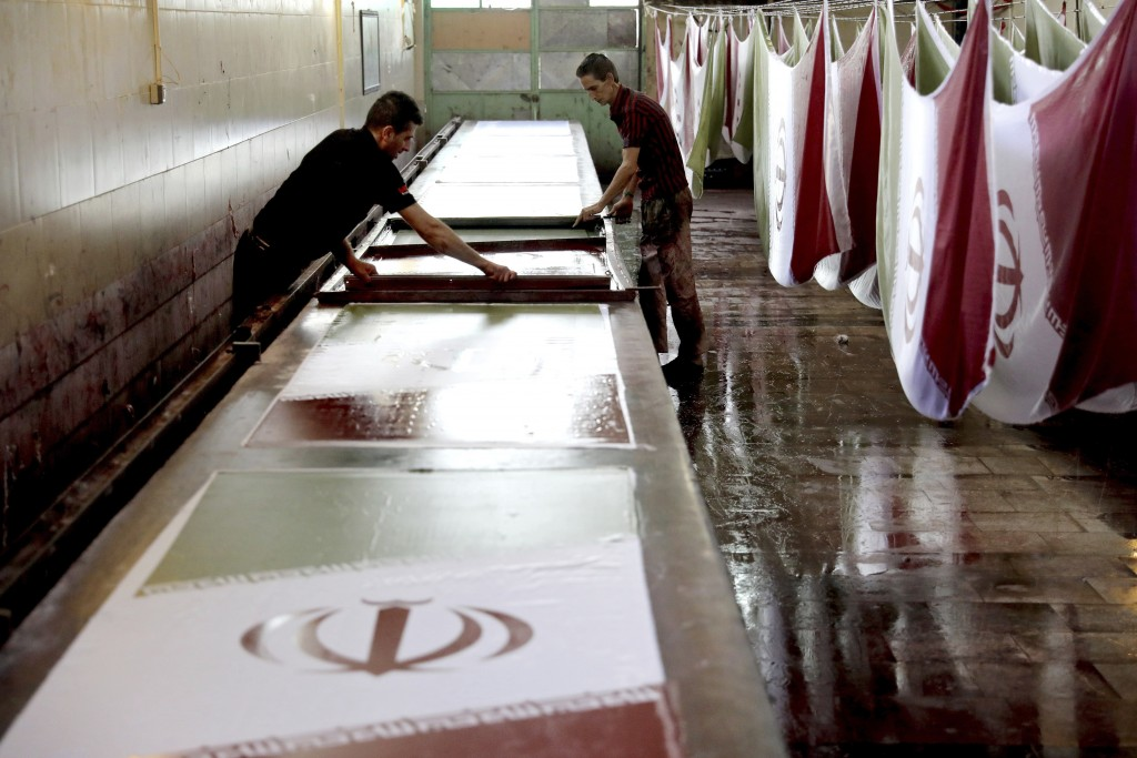In this Saturday, Feb. 8, 2020 photo, workers use a silk screen to print Iranian flags at the Diba Parcham Khomein factory in Heshmatieh village, a su...