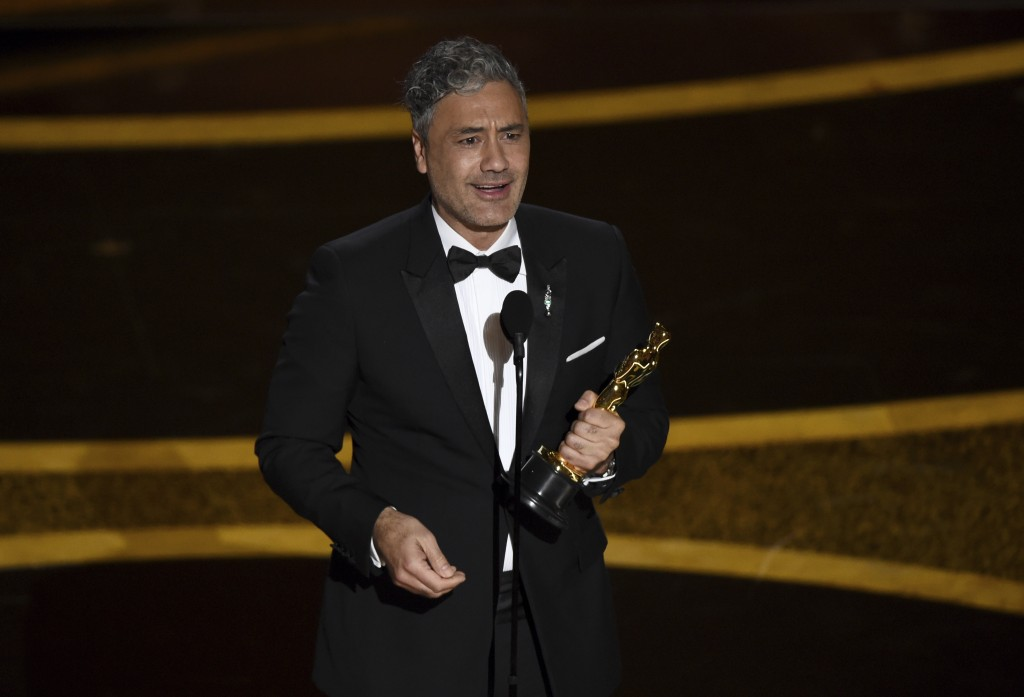 "Taika Waititi accepts the award for best adapted screenplay for ""Jojo Rabbit"" at the Oscars on Sunday, Feb. 9, 2020, at the Dolby Theatre in Los Angel..."