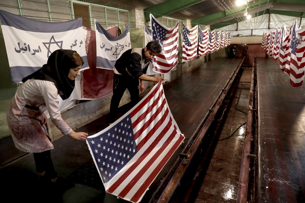 """In this Saturday, Feb. 8, 2020 photo, workers hang U.S. flags and Israeli flags with a slogan in Persian which reads, """"Death to Israel,"""" at the Diba P..."""