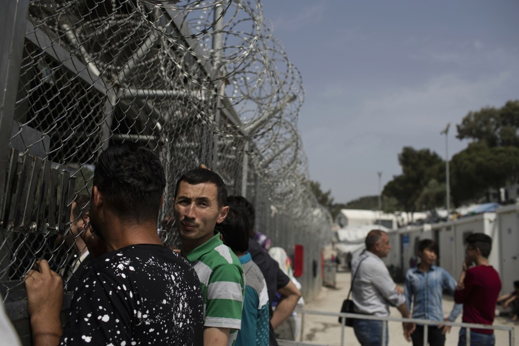 FILE - In this Friday, May 4, 2018 file photo, migrants and refugees wait outside the European Asylum Support Service offices inside the camp of Moria...