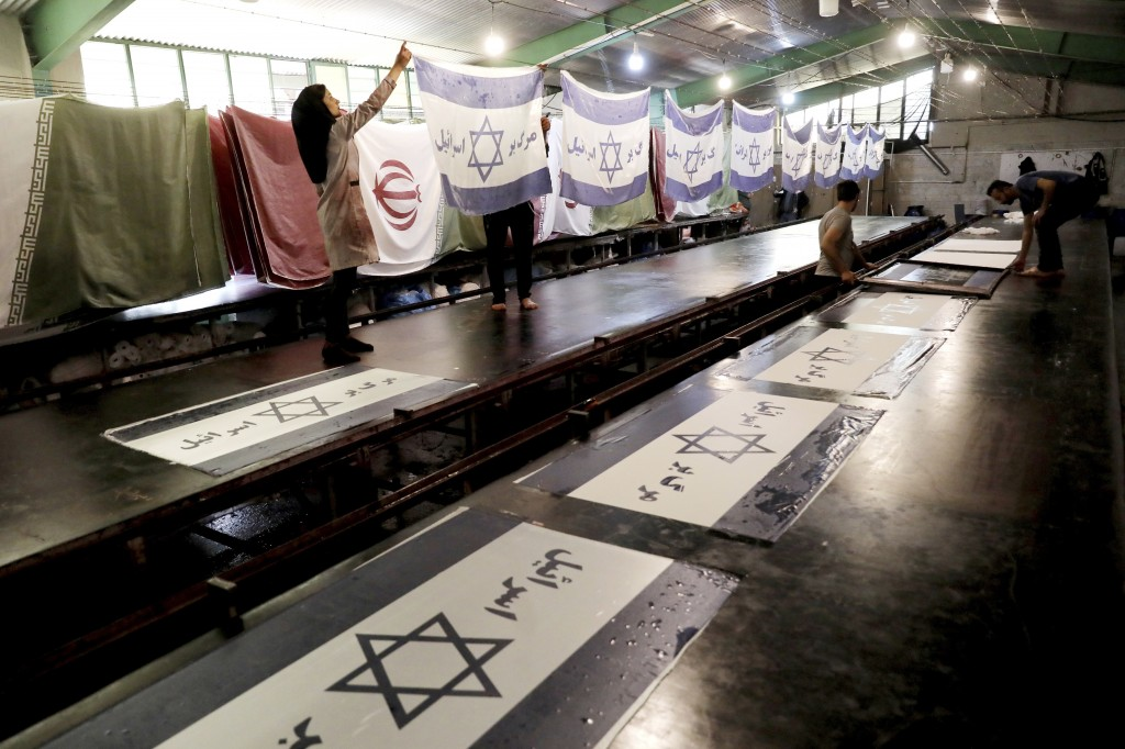 """In this Saturday, Feb. 8, 2020 photo, workers print Israeli flags with a slogan in Persian which reads, """"Death to Israel"""" at the Diba Parcham Khomein ..."""
