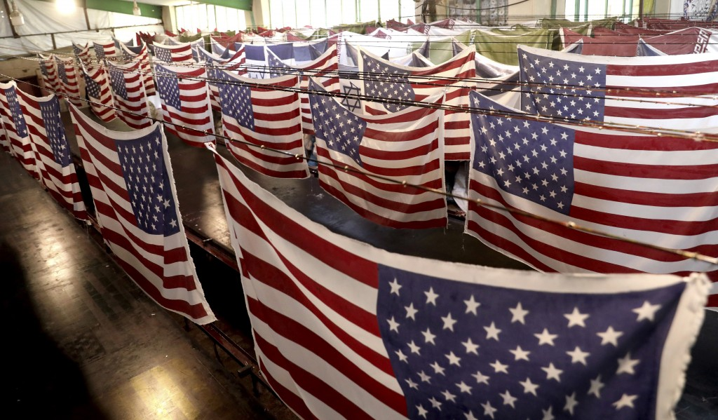 In this Saturday, Feb. 8, 2020 photo, U.S. flags hang to dry at the Diba Parcham Khomein factory in Heshmatieh village, a suburb of Khomein city, in c...
