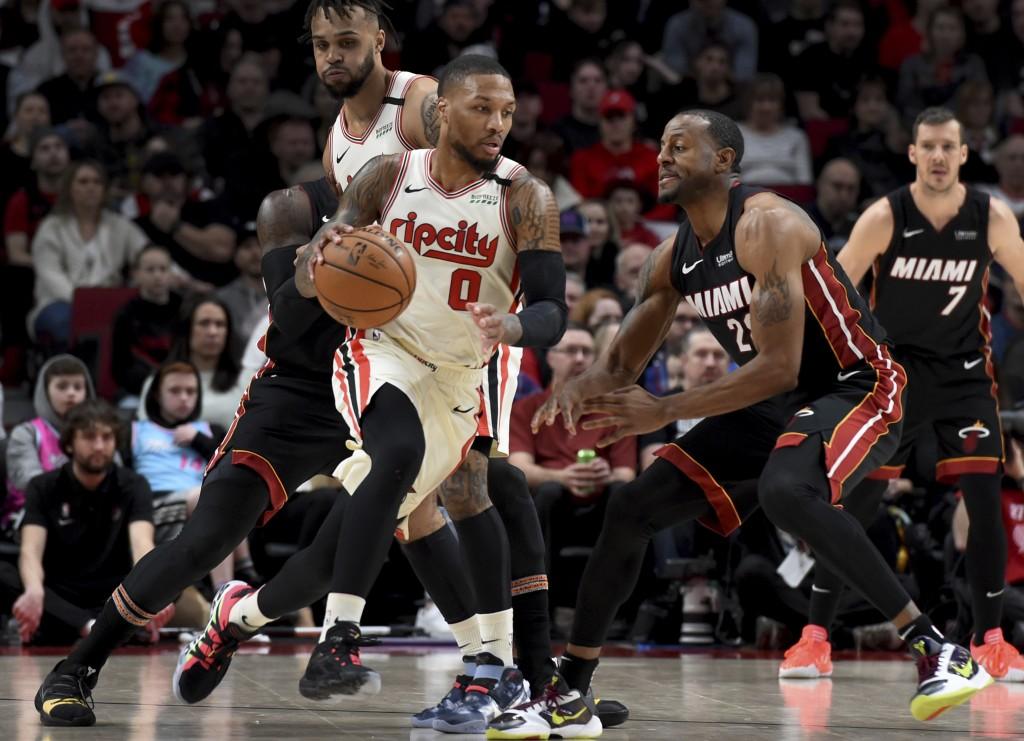 Portland Trail Blazers guard Damian Lillard, left, dribbles the ball around, Miami Heat guard Andre Iguodala, right, during the first half of an NBA b...
