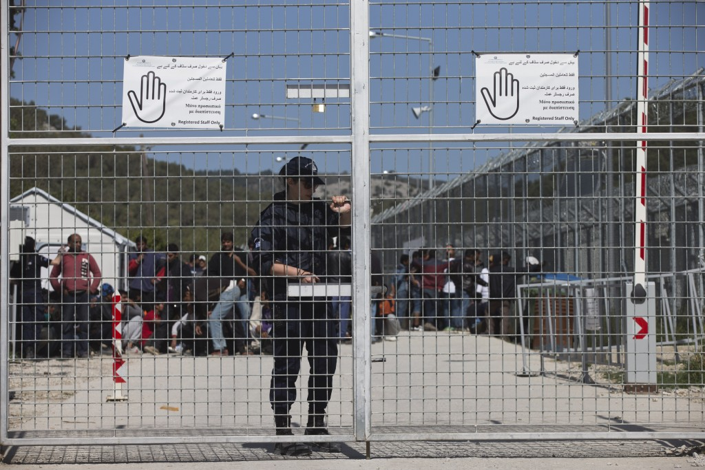 FILE - In this Tuesday, April 5, 2016 file photo, a Greek police officer closes the main gate of Moria camp as behind her refugees and migrants protes...