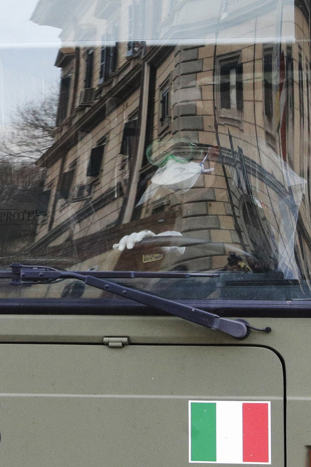 A soldier wearing protective mask drives a military bus with Italians evacuated from Wuhan, China, as it arrives at an army complex in Rome, Sunday, F...