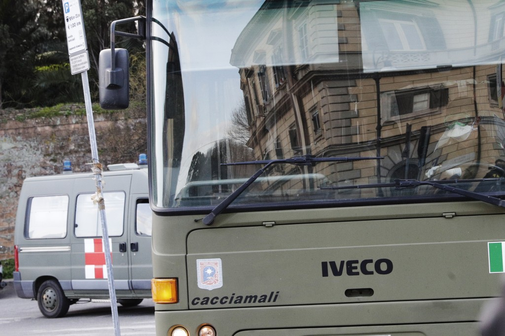Italians evacuated from Wuhan, China, on a military bus arrive at at an army complex in Rome, Sunday, Feb. 9, 2020. The Italian foreign ministry said ...