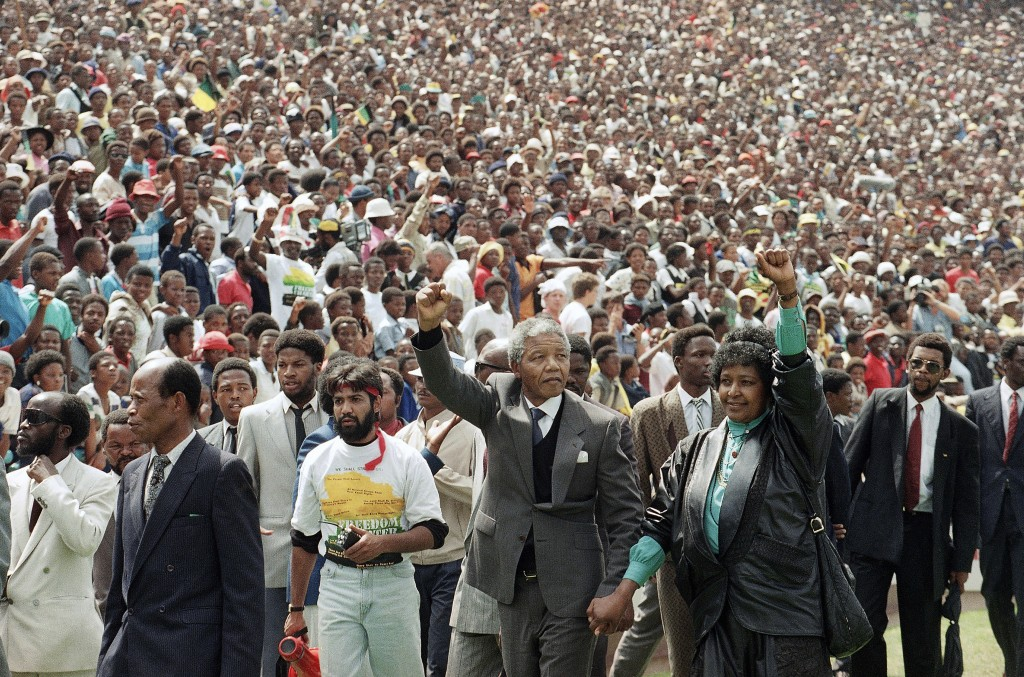 FILE - In this Feb. 13, 1990 file photo, Nelson Mandela and his wife, Winnie Madikizela-Mandela, gesture as they arrive at Soccer City Stadium in Sowe...