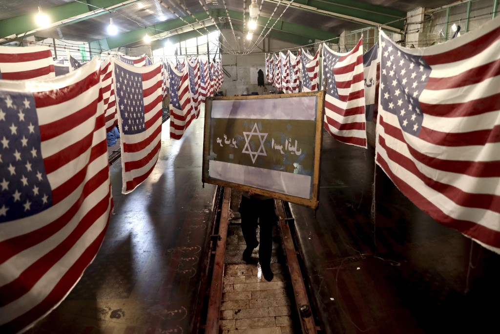 """In this Saturday, Feb. 8, 2020 photo, a worker carries a silk-screen stencil of an Israeli flag with a slogan in Persian which reads, """"Death to Israel..."""