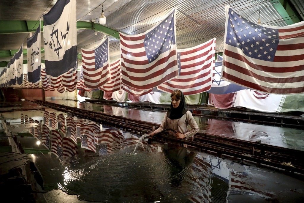 In this Saturday, Feb. 8, 2020 photo, a worker washes silkscreen printing platform under U.S. flags and Israeli flags with slogan in Persian which rea...