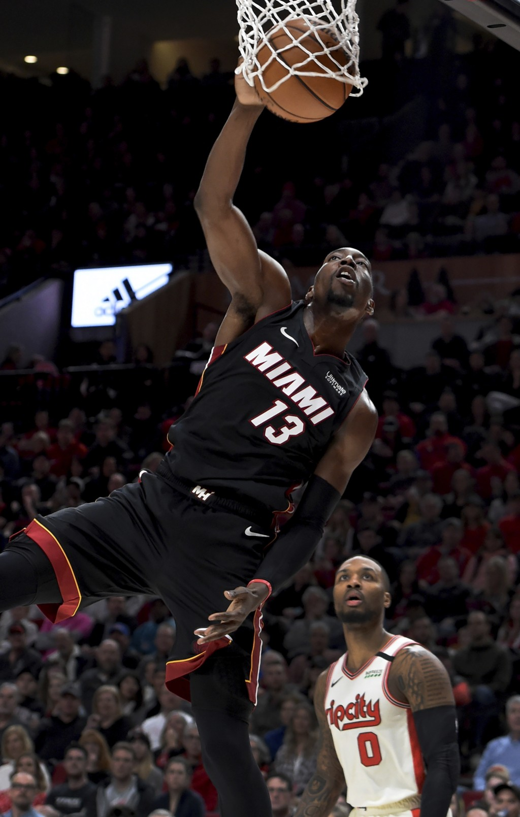 Miami Heat forward Bam Adebayo, left, dunks the ball as Portland Trail Blazers guard Damian Lillard, right, looks on during the first half of an NBA b...
