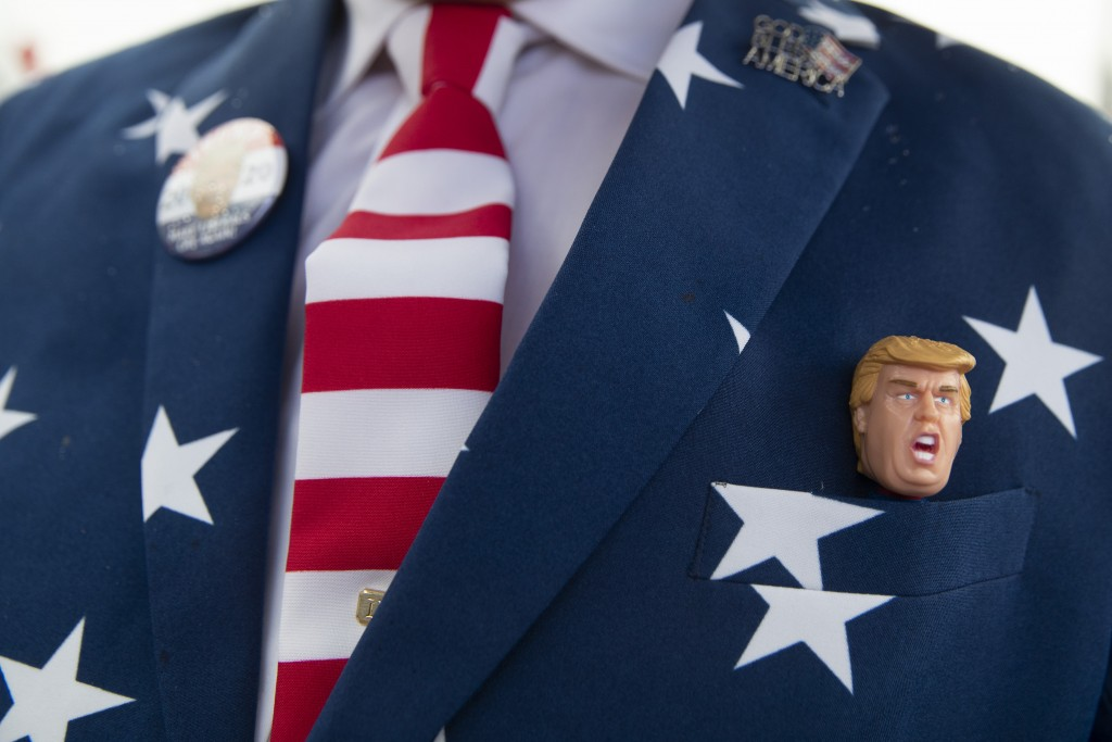 Richard Desrosiers, of Cape Cod, Mass., wears a suit and tie in the colors of the American Flag with and a figurine of President Donald Trump while wa...