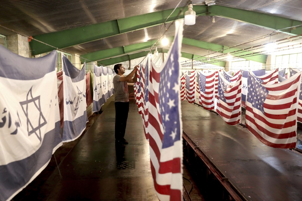 """In this Saturday, Feb. 8, 2020 photo, a worker hangs U.S. flags to dry alongside Israeli flags with a slogan in Persian which reads, """"Death to Israel,..."""