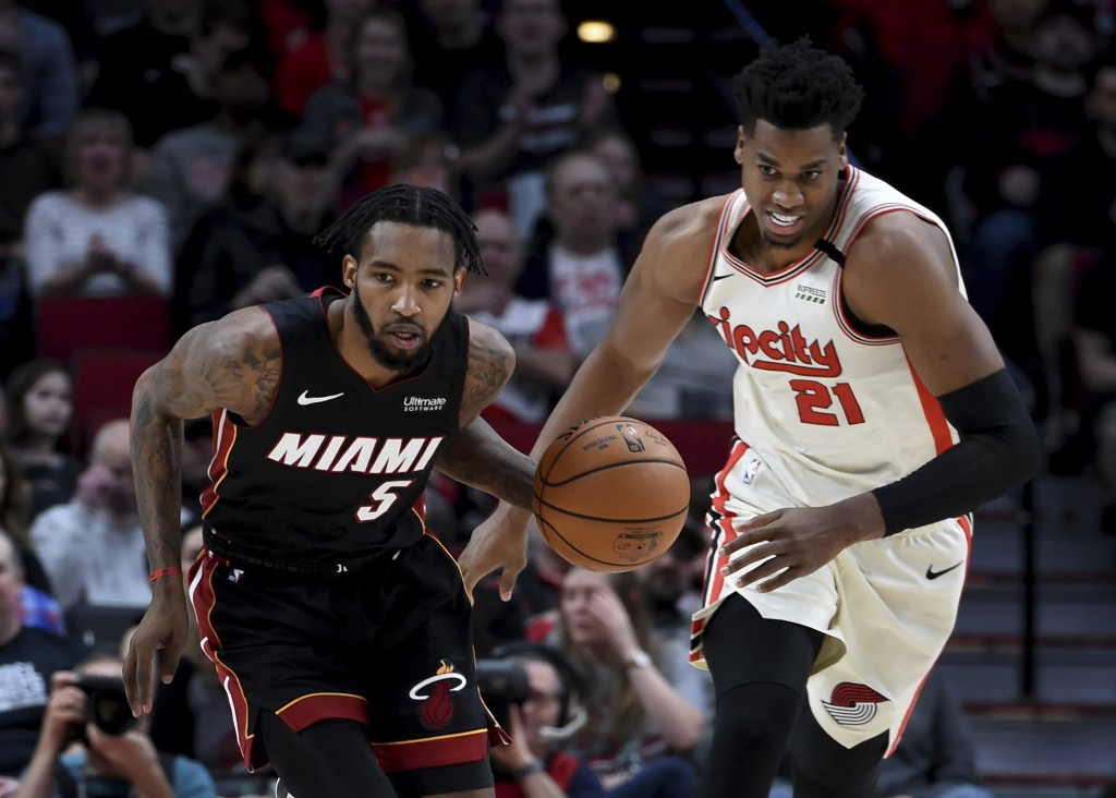 Miami Heat forward Derrick Jones Jr., left, heads up the court with the ball as Portland Trail Blazers center Hassan Whiteside, right, gives chase dur...