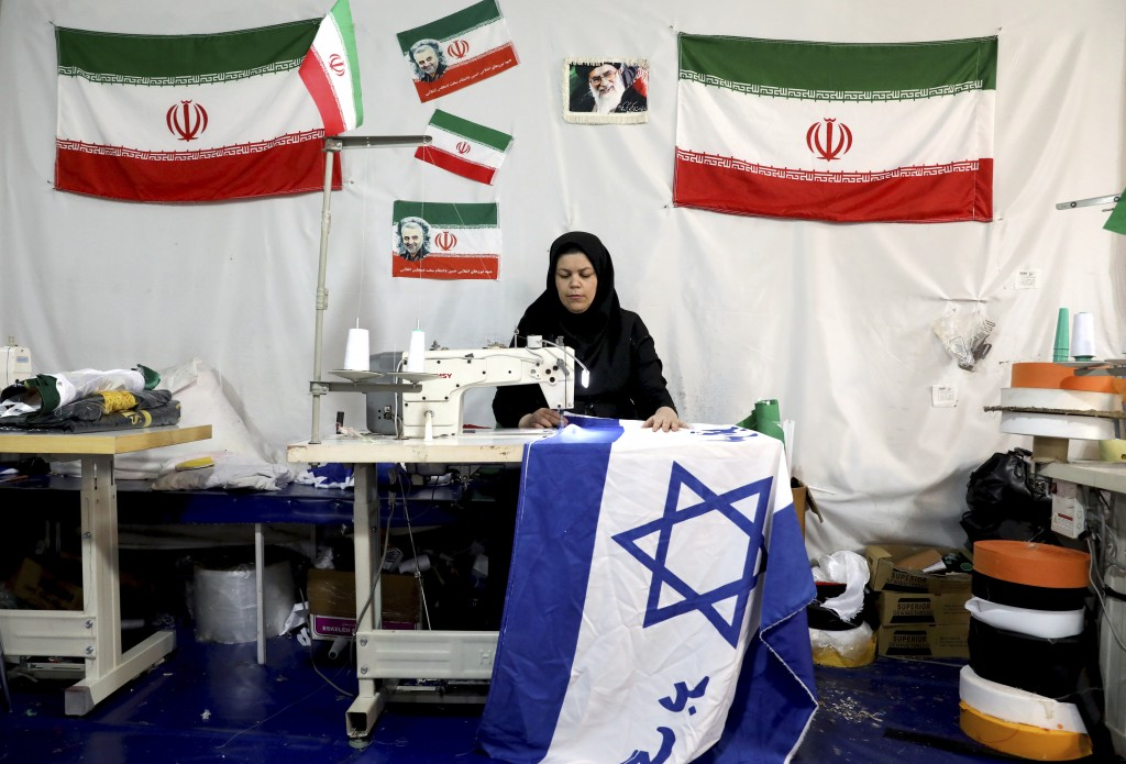 """In this Saturday, Feb. 8, 2020 photo, a worker sews an Israeli flag with a slogan in Persian which reads, """"Death to Israel,"""" at the Diba Parcham Khome..."""