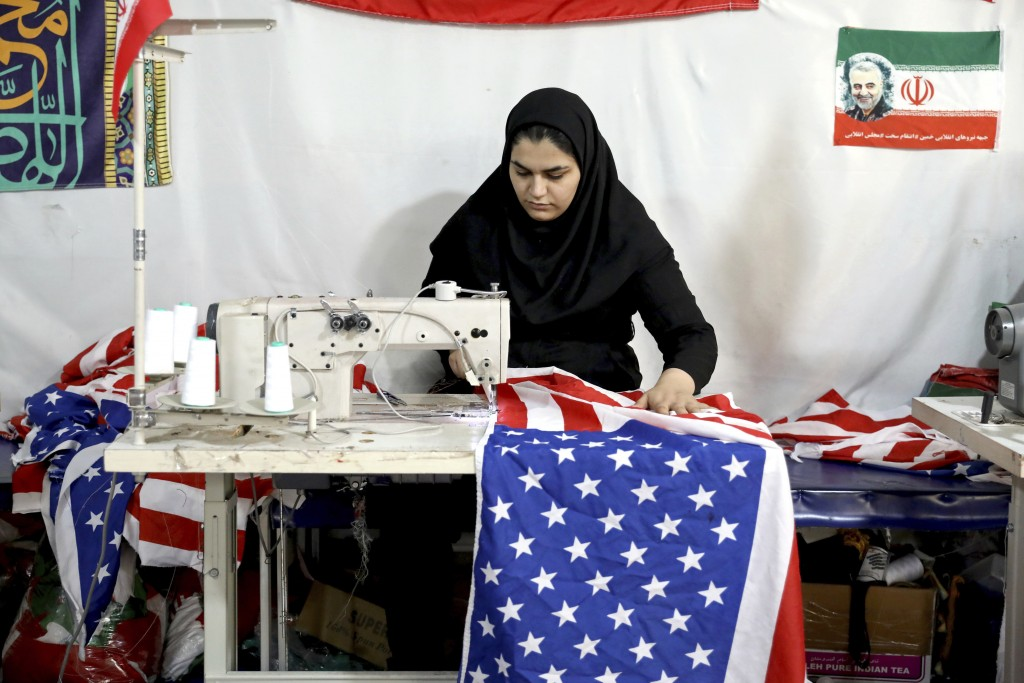 In this Saturday, Feb. 8, 2020 photo, a worker sews a U.S. flag at the Diba Parcham Khomein factory in Heshmatieh village, a suburb of Khomein city, i...