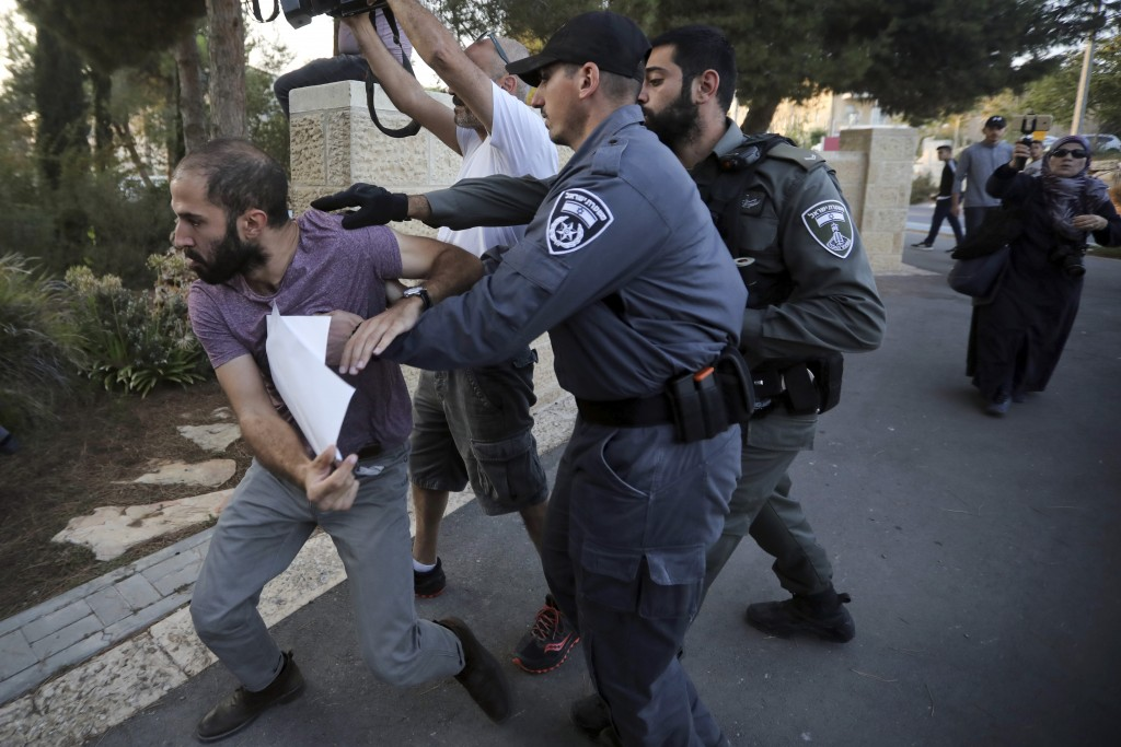 FILE - In this Oct. 1, 2019 file photo, Israeli police push a man during a protest outside a hospital in Jerusalem where Samir Arbeed, a Palestinian s...