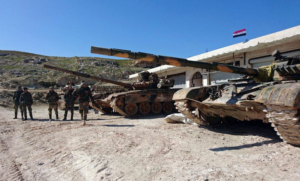 In this photo released by the Syrian official news agency SANA, Syrian government forces entering the village of al-Eis, in Aleppo province, Syria, Su...