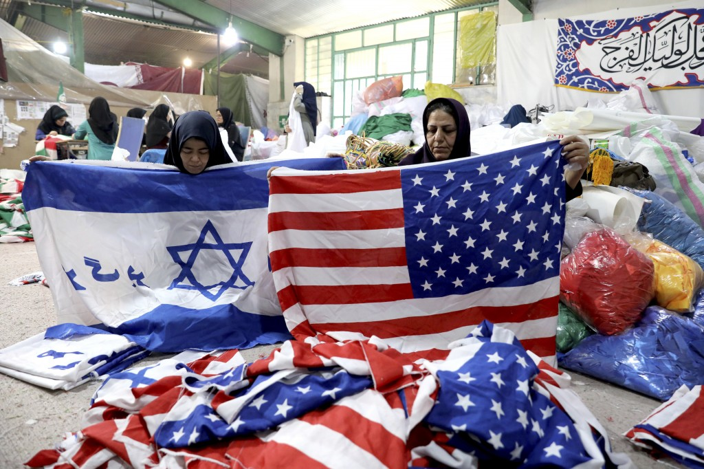 """In this Saturday, Feb. 8, 2020 photo, workers fold U.S. flags and Israeli flags with a slogan in Persian which reads, """"Death to Israel"""" at the Diba Pa..."""