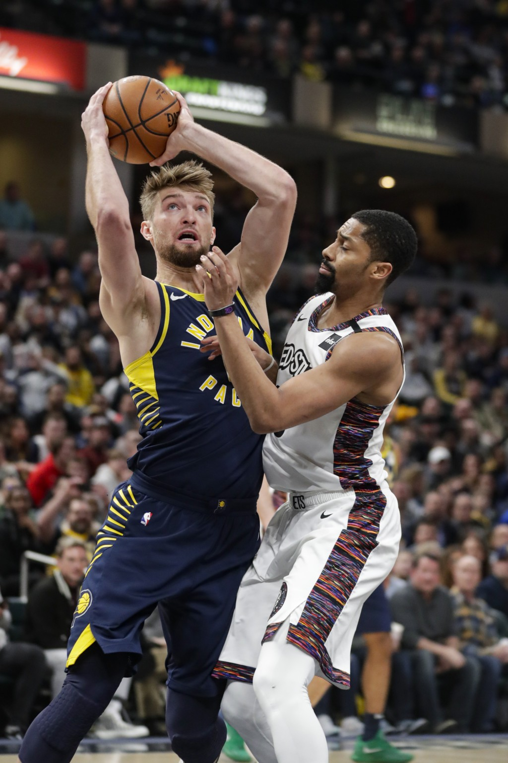 Indiana Pacers forward Domantas Sabonis, left, shoots over Brooklyn Nets guard Spencer Dinwiddie, right, during the first half of an NBA basketball ga...