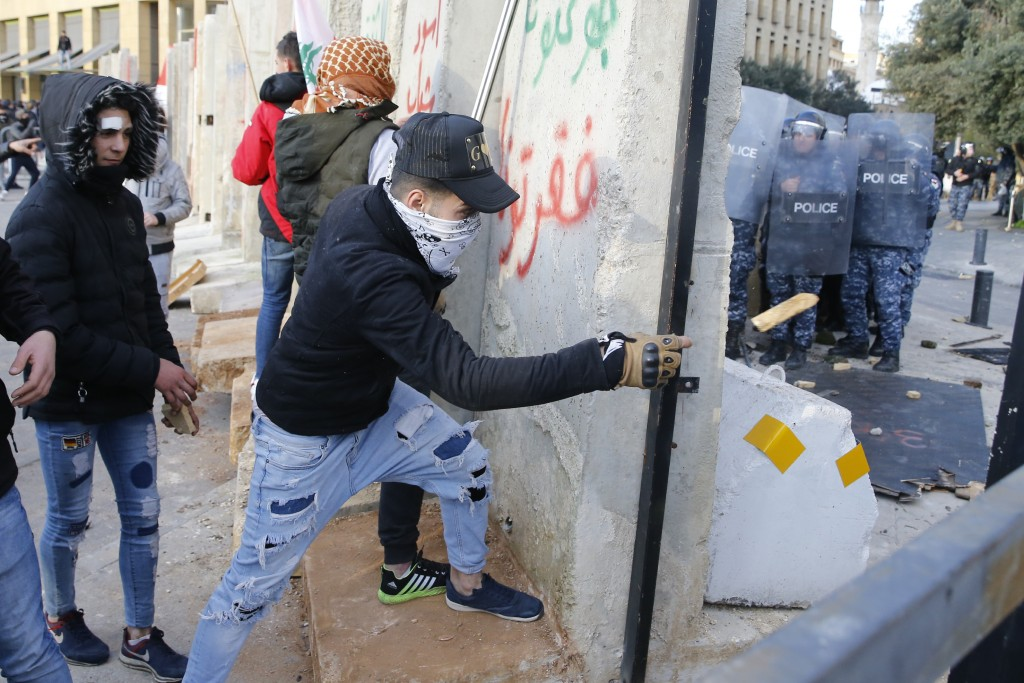 Demonstrators throw stones toward riot police during a protest against a parliament session preparing a vote of confidence for the new government in d...