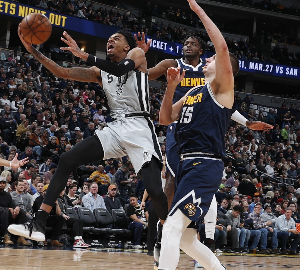 San Antonio Spurs guard Dejounte Murray, left, drives to the rim past Denver Nuggets center Nikola Jokic, front right, and forward Jerami Grant in the...