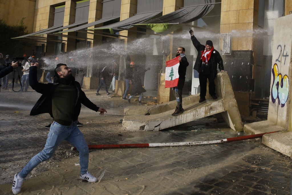 Anti-government demonstrators throw stones toward riot police during a protest against a parliament session for a vote of confidence for the new gover...