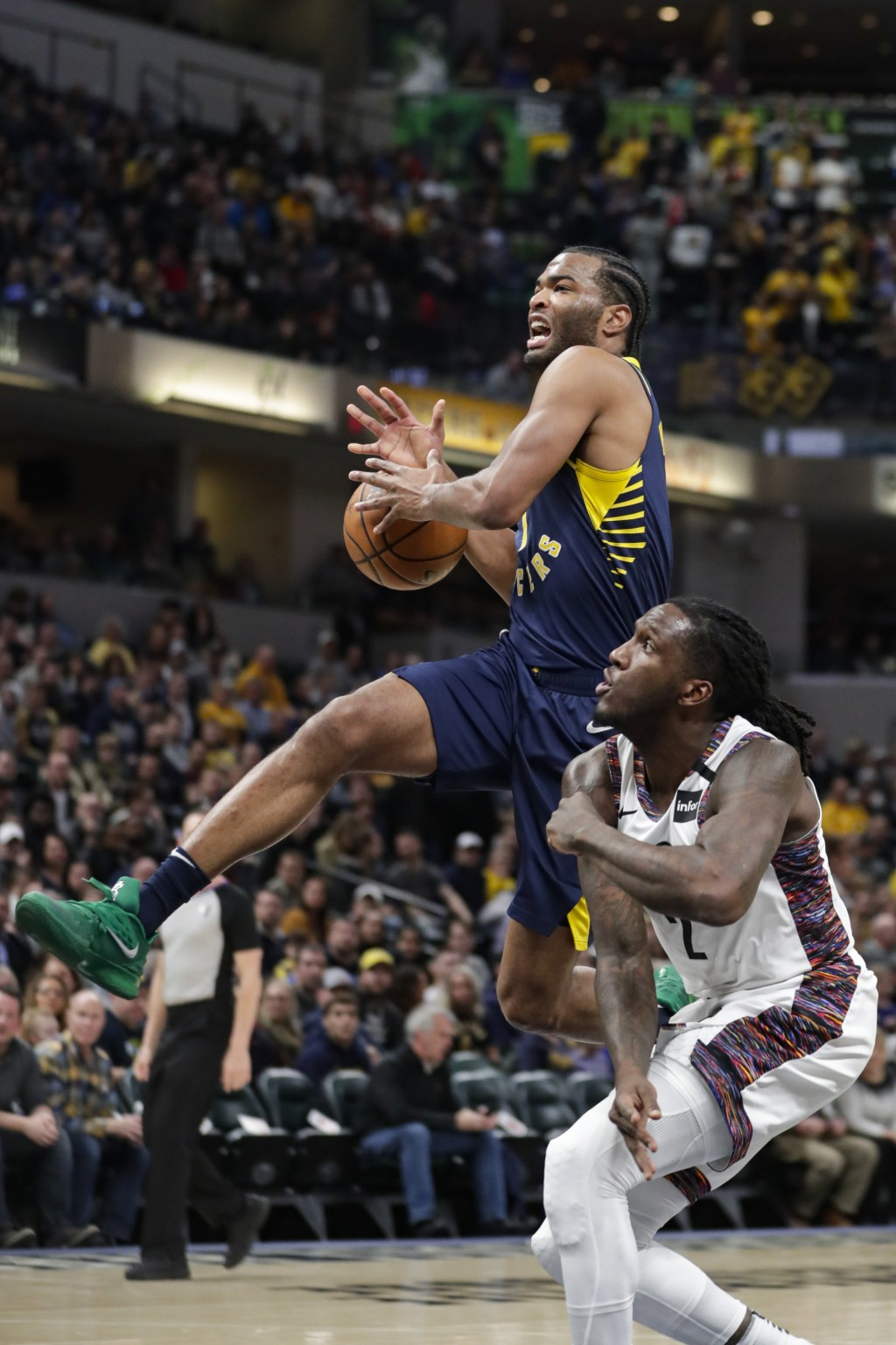 Indiana Pacers forward T.J. Warren, top, loses the ball as he goes to the bucket over Brooklyn Nets forward Taurean Prince (2) during the first half o...
