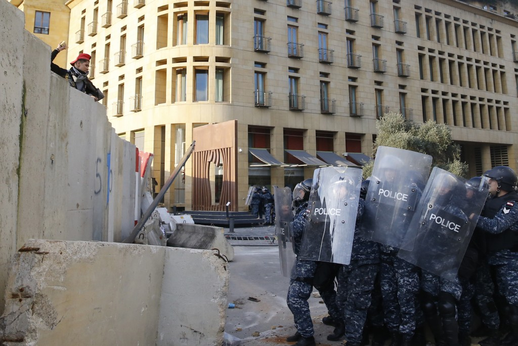 An anti-government demonstrator throws stones toward riot police on a road leading to the parliament building, during a protest against a parliament s...