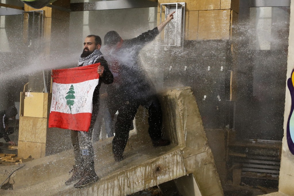 Riot police spray anti-government protesters with water cannons during a protest against a parliament session preparing a vote of confidence for the n...