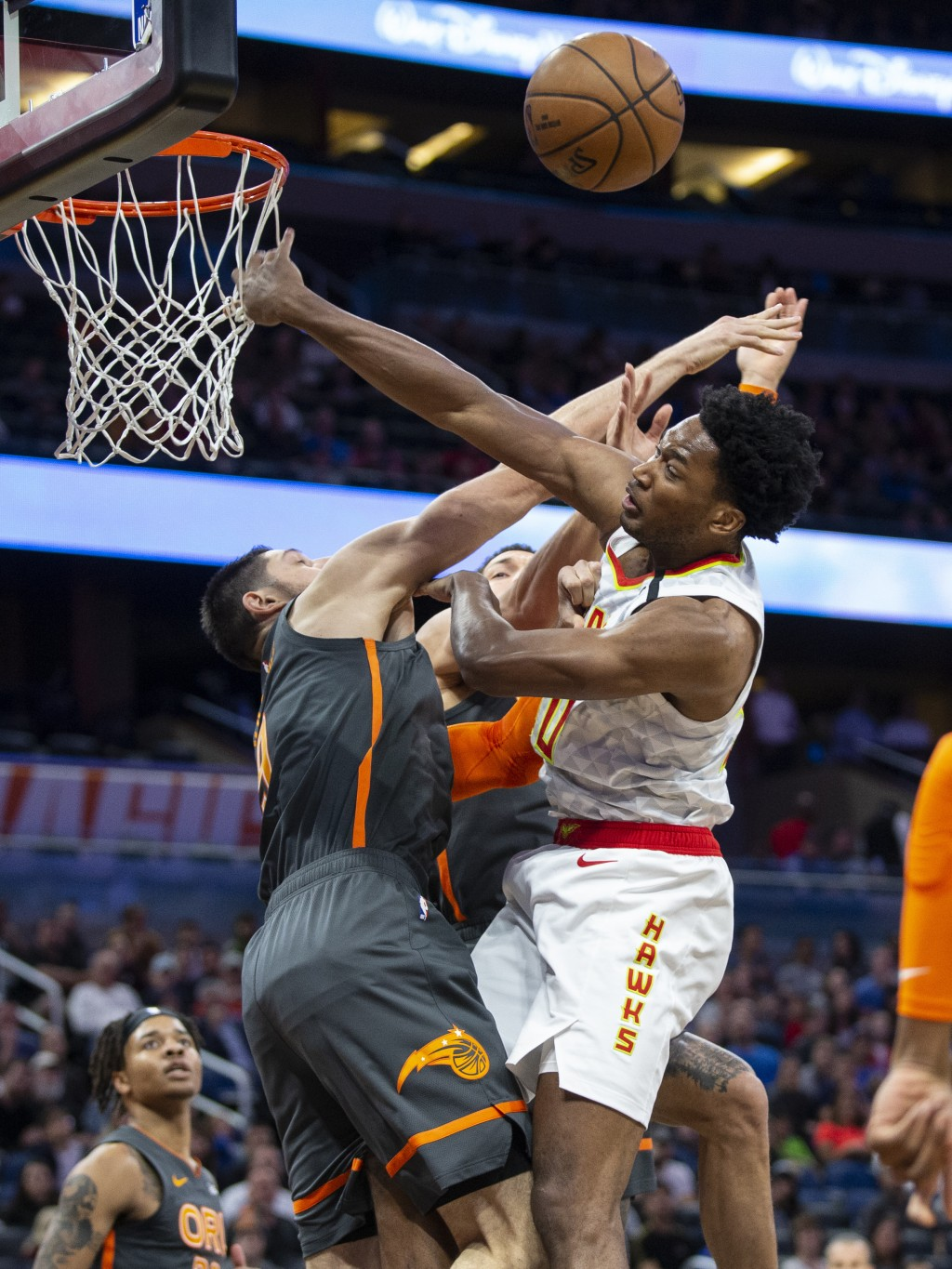 Orlando Magic center Nikola Vucevic, left, and Atlanta Hawks center Damian Jones, right, fight for a rebound during the first half of an NBA basketbal...
