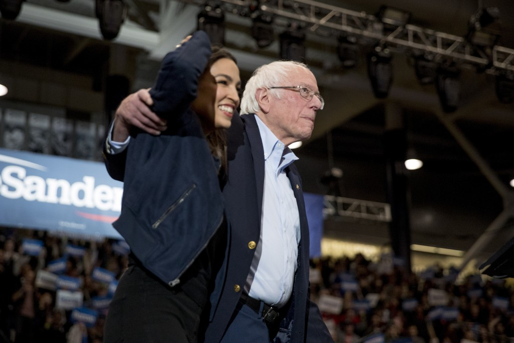Democratic presidential candidate Sen. Bernie Sanders, I-Vt., accompanied by Rep. Alexandria Ocasio-Cortez, D-N.Y., left, takes the stage at campaign ...