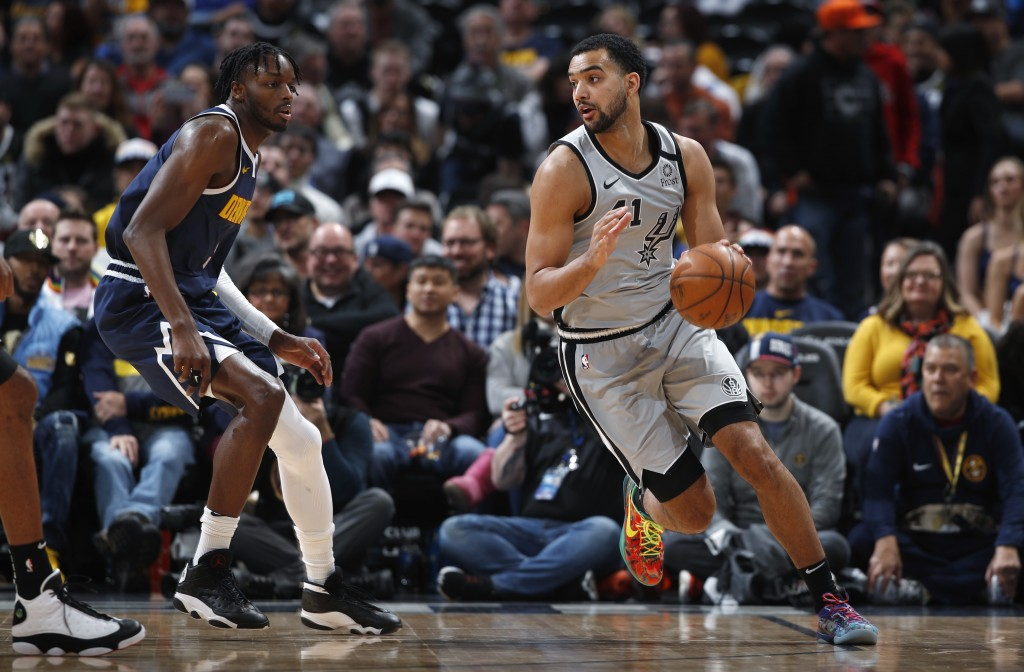 San Antonio Spurs center Trey Lyles, right, drives past Denver Nuggets forward Jerami Grant in the first half of an NBA basketball game Monday, Feb. 1...