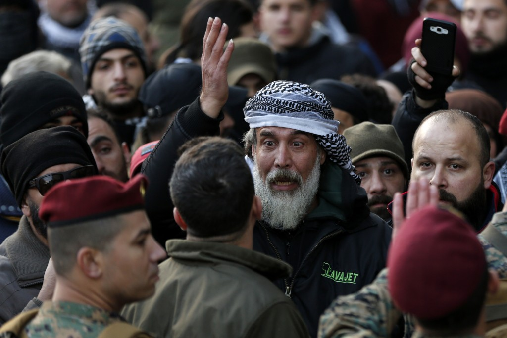 An anti-government protester argues with Lebanese army special forces during a protest against a parliament session to vote of confidence for the new ...