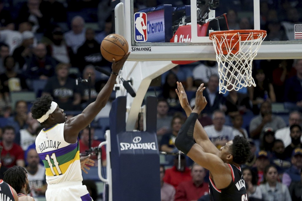 New Orleans Pelicans guard Jrue Holiday (11) shoots as Portland Trail Blazers center Hassan Whiteside (21) defends in the first half of an NBA basketb...