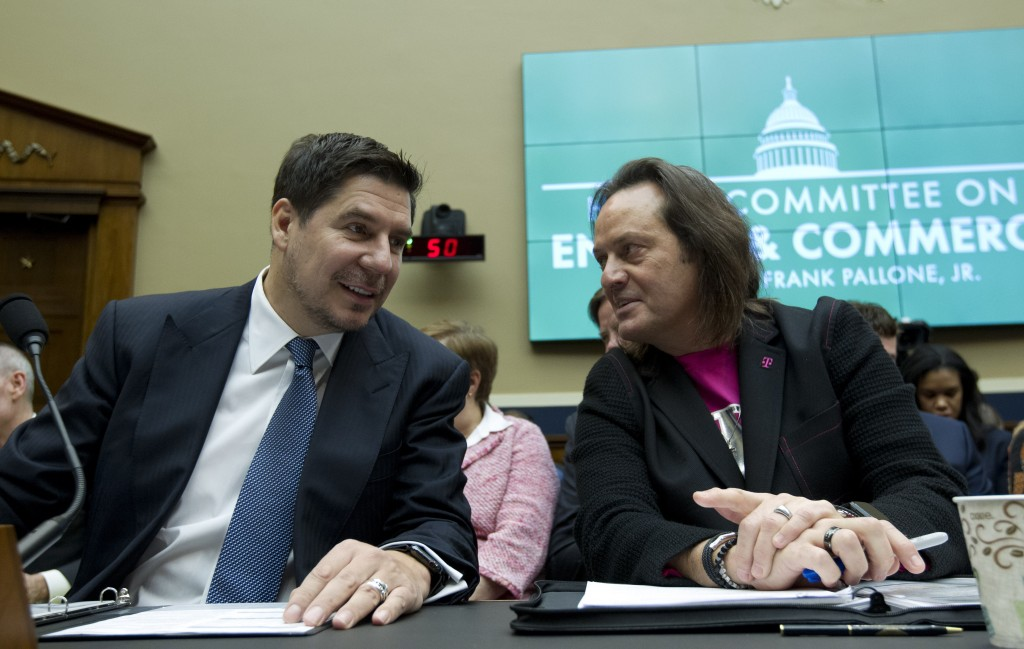 FILE - In this Feb. 13, 2019, file photo Sprint Corporation Executive Chairman Marcelo Claure, left, speaks with T-Mobile US CEO and President John Le...
